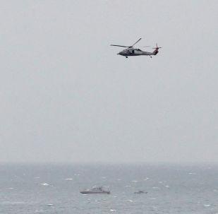 صورة أرشيفية: قارب تباع للحرس الثوري الإيراني بالقرب من حاملة الطائرات الأمريكية يو إس إس جورج بوش في مضيق هرمز، بينما تحلق طائرات الهليكوبتر التابعة للبحرية الأمريكية بالقرب من المكان، 21 مارس/ آذار 2017