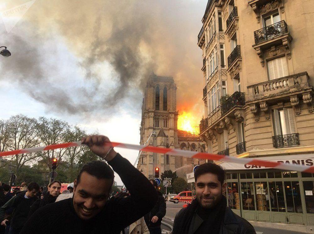 أشخاص بالقرب من موقع اندلاع الحريق في كتدرائية نوتر دام في باريس