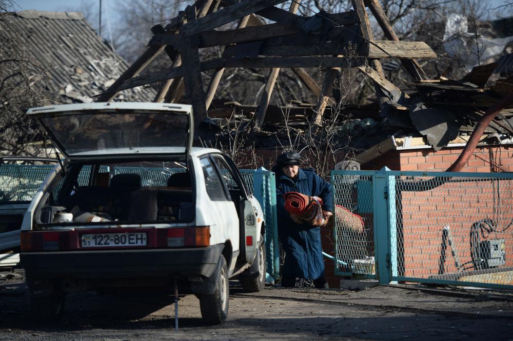 امرأة تخرج أغراضها من منزلها المدرمر بعد الاشتباكات بالقرب من المطار في مدينة دونيتسك