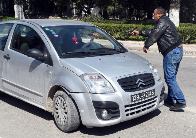 شرطي في لباس مدني يوقف سيارة في مكان حادثة الهجوم الارهابي في تونس