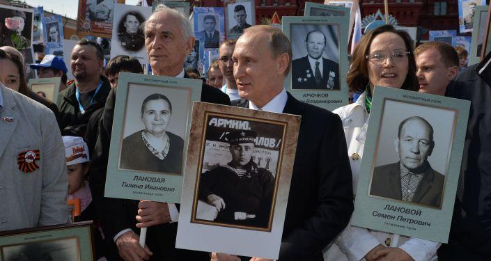بوتين يحمل صورة والده الذي اشترك في الحرب الوطنية العظمى