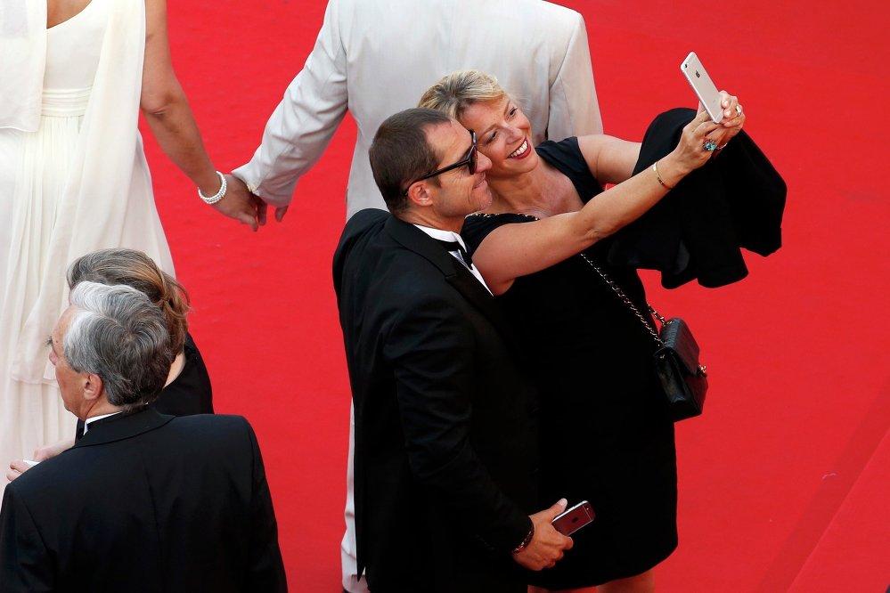 جانب من الحضور يلتقطون السيلفي خلال مهرجان كان السينمائي الـ 68، جنوب فرنسا، 13 مايو 2015.