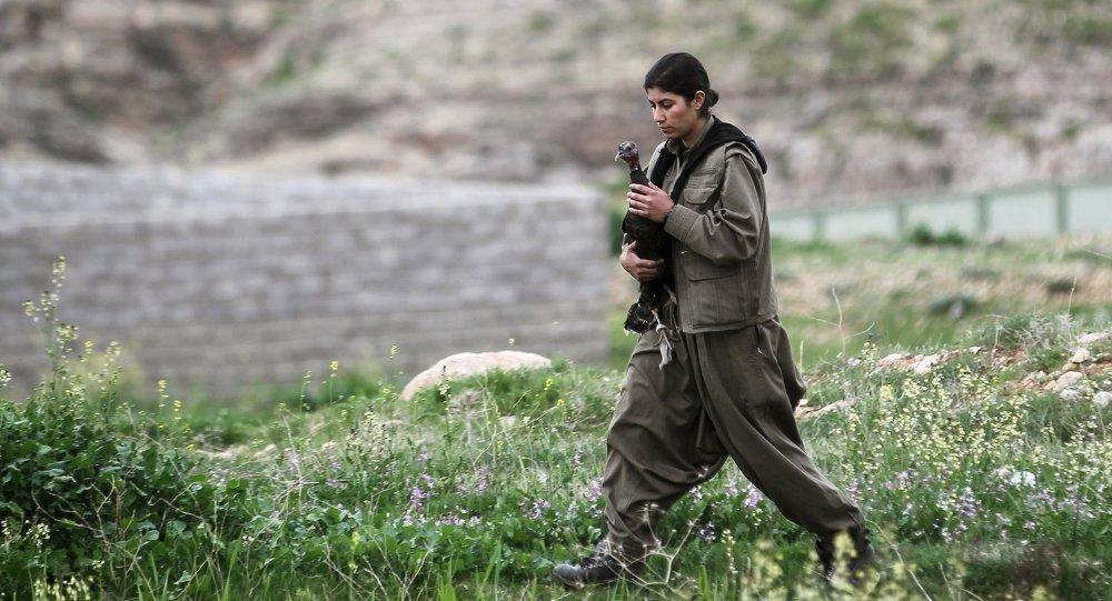 مقاتلة كردية فى جبل سنجار لا تنسى أعمال المرأة  المنزلية الى جانب حمل السلاح للدفاع عن وطنها