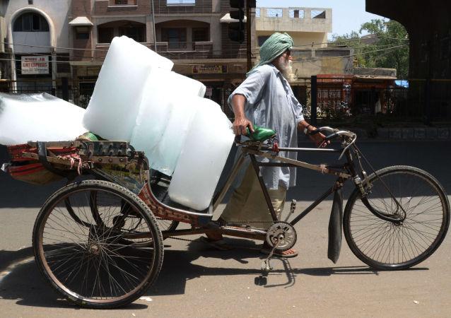 مواطن هندي ينقل الجليد أثناء موجة الحر