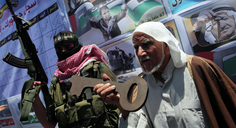 Palestinian militants of the Ezzedine al-Qassam Brigades, Hamas' armed wing, stand with an old Palestinian man holding a wooden key during a parade in the southern Gaza Strip town of Rafah on May 17, 2015 to mark the 67th anniversary of the Nakba