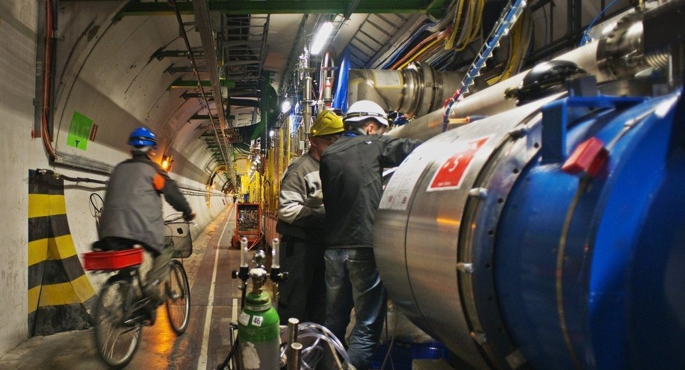 An engineer on a bicycle provided for tunnel transportation rides past engineers working on the Large Hadron collider in the 27Km circular tunnel at CERN near Geneva in the planned 2013 shutdown