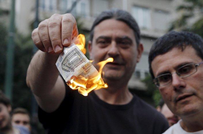 متظاهر يوناني يحرق عملة اليورو خلال مسيرة إحتجاجية ضد الإتحاد الأوروبي فى أثينا