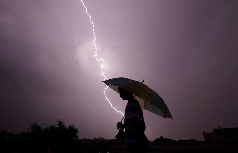أحد المارة أثناء حدوث البرق فى الهند