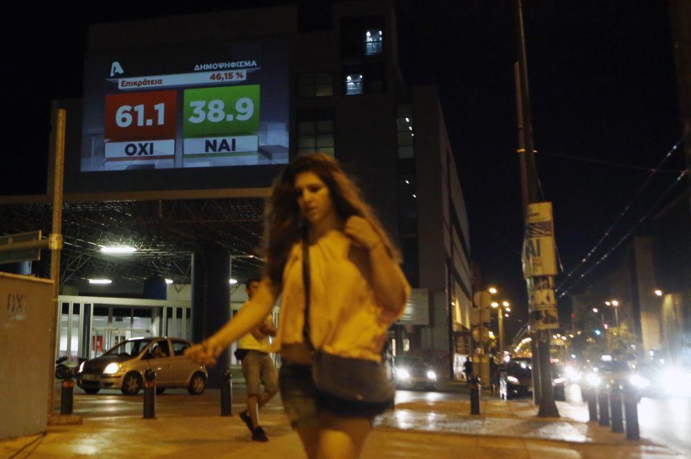فتاة تسير فى شوارع أثينا وفى الخلفية نتيجة الاستفتاء التى تظهر ارتفاع مؤشر الرفض