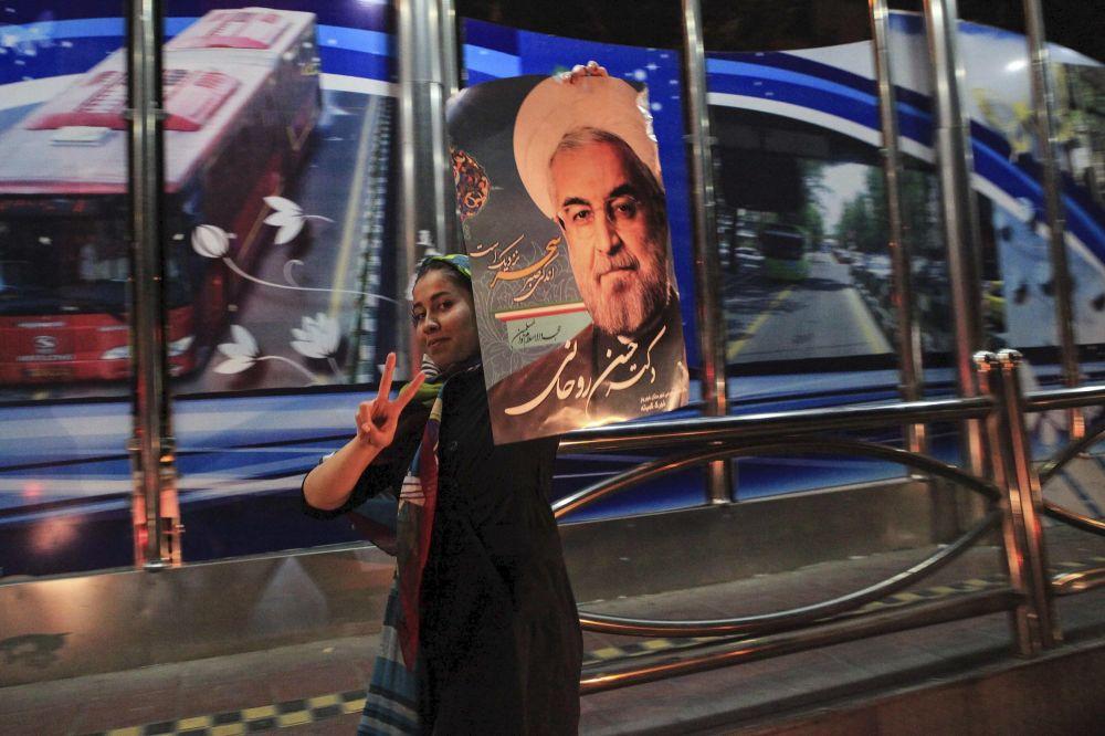 فتاة تحمل صورة الرئيس الإيراني حسن روحاني احتفالاً بالاتفاق النووي