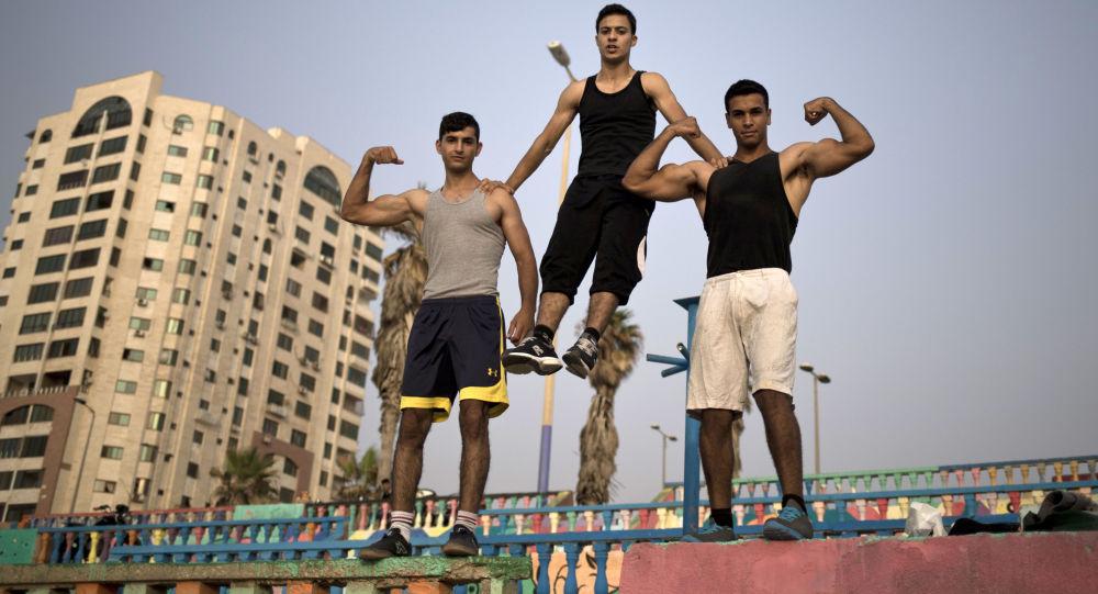 شباب غزة يعرضون عضلاتهم في أحد الشوارع بالقرب من شاطئ البحر