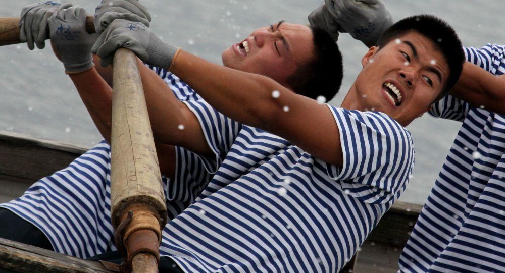 البحارة الصينيون خلال سباق على متن قوارب، أثناء التدريبات الروسية الصينية التعاون البحري – 2015  في مدينة  فلاديفوستوك
