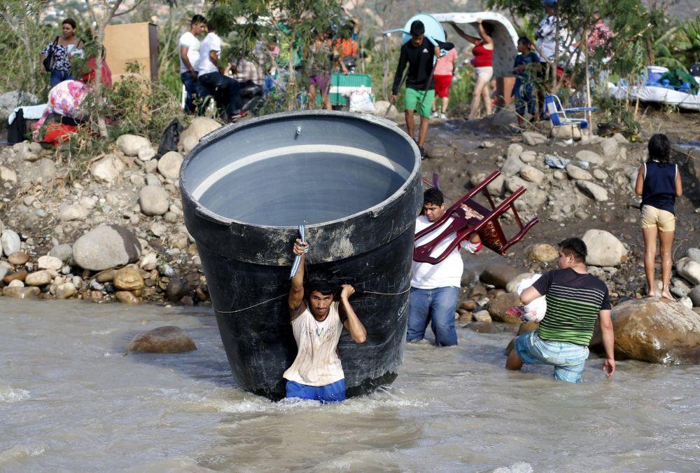 ناس ينقلون أمتعتهم عبر النهر على الحدود بين فنزويلا وكولومبيا