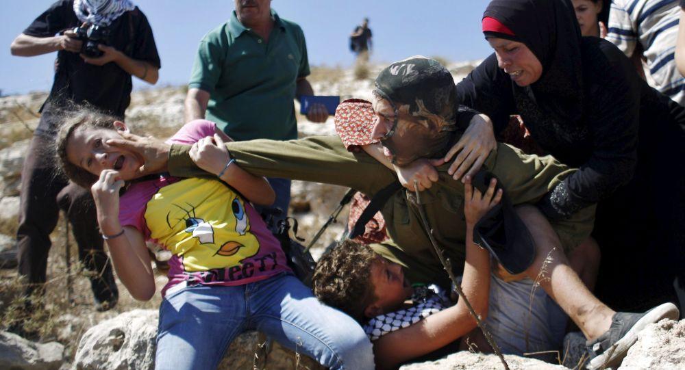نساء فلسطينيات يصارعن جندي إسرائيلي لمنعه من اعتقال فتى خلال احتجاجات ضد المستوطنات اليهودية في الضفة الغربية في قرية النبي صالح قرب رام الله 28 أغسطس/ آب 2015.