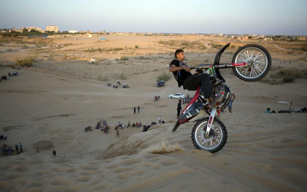 شاب فلسطيني يقوم بخدع رياضية على دراجته النارية.