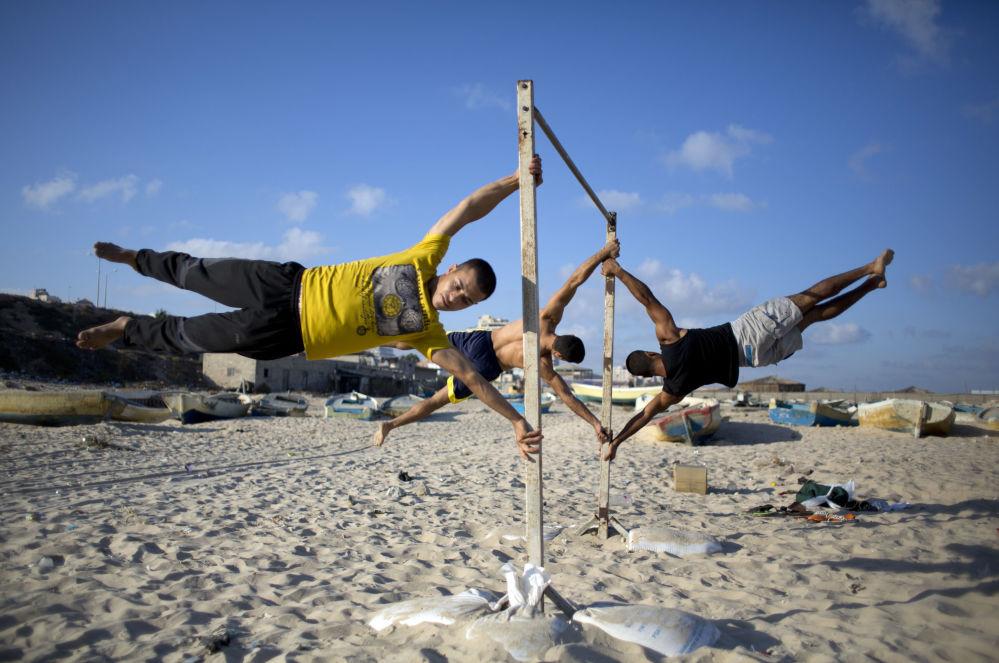شبان فلسطنيون يمارسون تمارين رياضية على شاطئ ساحل قطاع غزة.