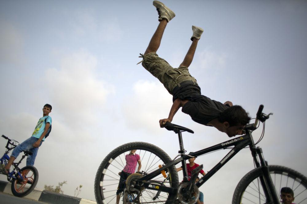 شاب فلسطيني أثناء قيامه بحركة بهلوانية باستخدام دراجته