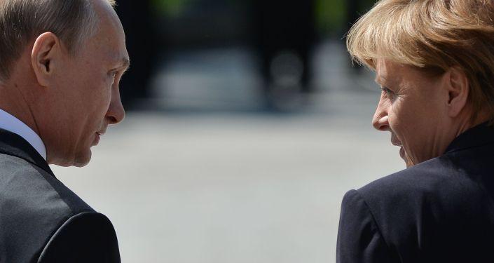 الرئيس الروسي فلاديمير بوتين والمستشارة الألمانية انجيلا ميركل أثناء مراسم وضع أكلاليل الزهور على قبر الجندي المجهول في حديقة الكسندر في موسكو