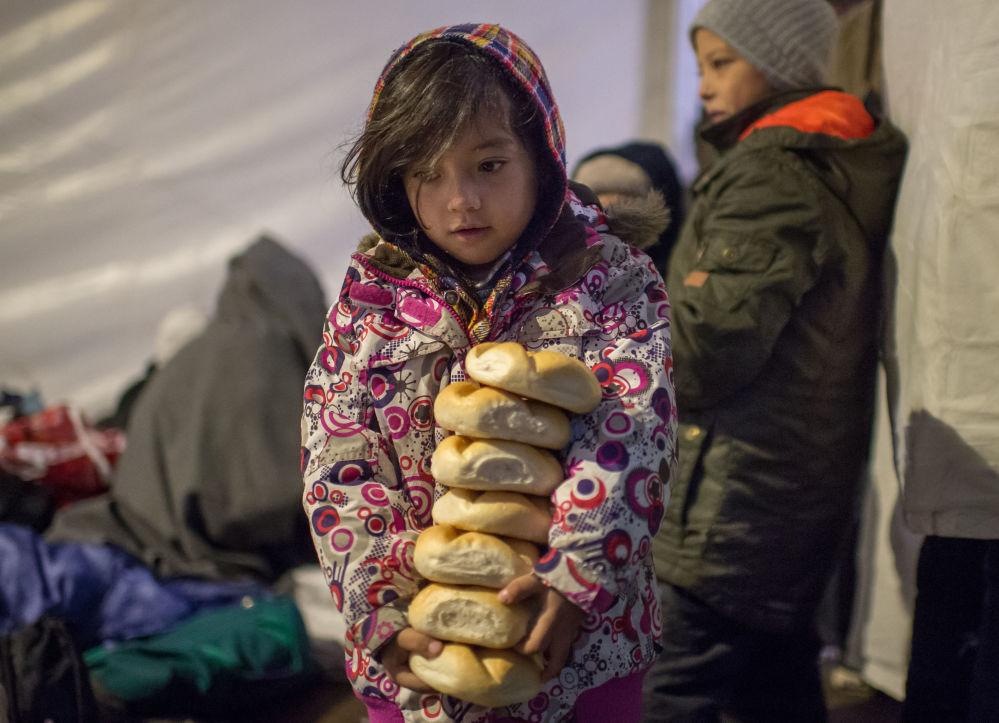 طفلة صغيرة تحمل فطائر ساخنة إلى خيمتها، حيث عائلتها، في بلدة هانغينغ المجرية، 3 نوفمبر/ تشرين الثاني 2015. ويذكر أن درجات الحرارة في الليل أصبحت تنخفض تحت الصفر.