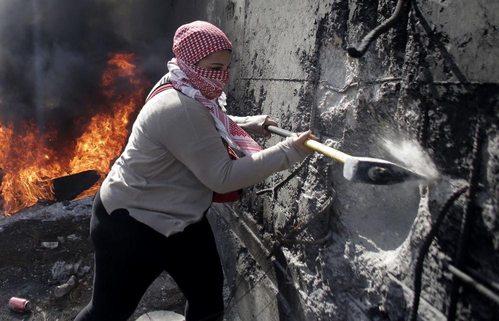 فتاة فلسطينية ملثمة تهدم جزءاً من الجدار الفاصل في القدس الشرقية، الضفة الغربية.