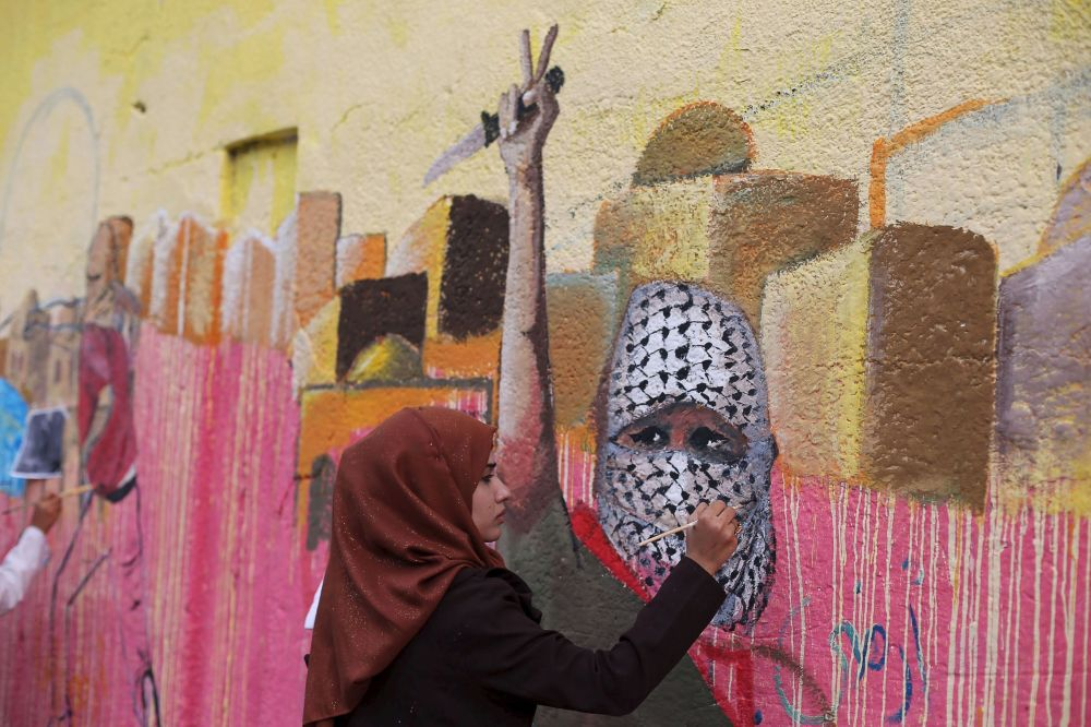 فتاة فلسطينية ترسم لوحة جدارية تضامناً مع أحداث الضفة الغربية، في مدينة رفح جنوب قطاع غزة، 3 نوفمبر/ تشرين الثاني 2015.