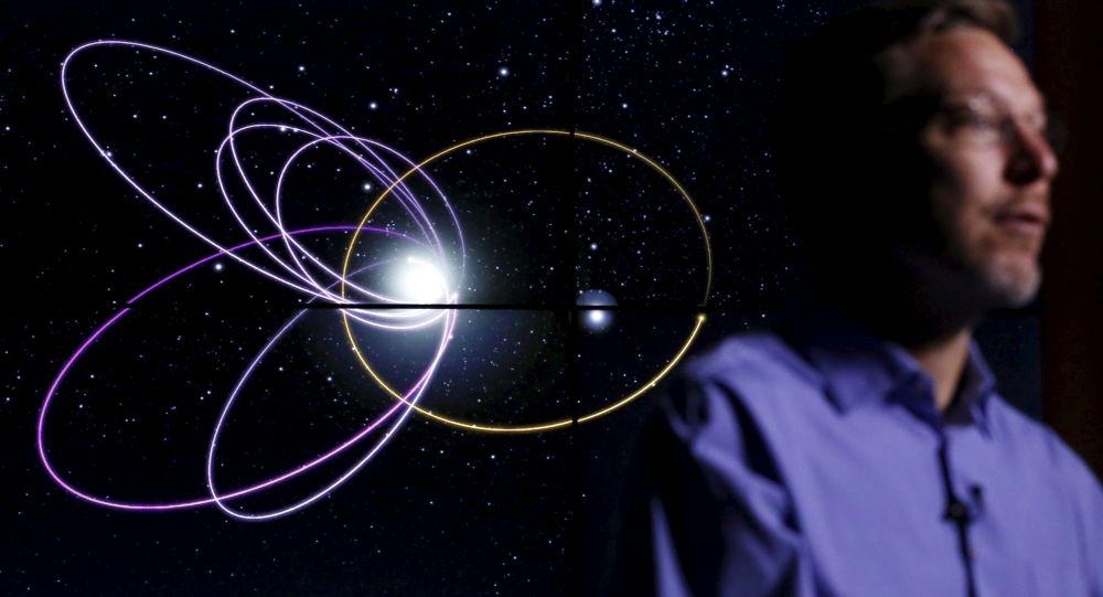 Профессор Майк Браун напротив изображения предположительной орбиты новой планеты Солнечной системы