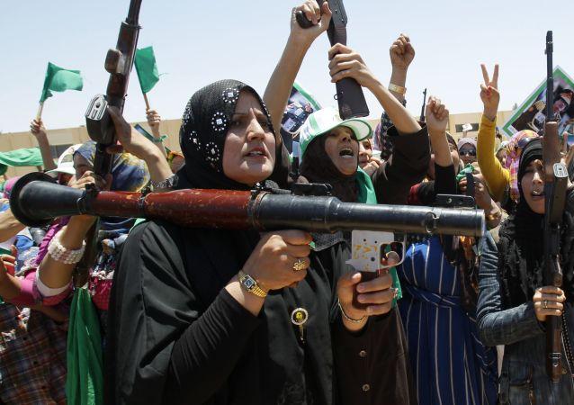 المواليات للقائد الليبي معمر القذافي تحملن السلاح خلال المواجهات الحربية في بلدة بن جواد في ليبيا