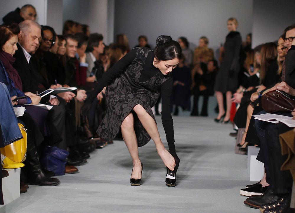 عارضة أزياء تعدّل حذائها أثناء عرض أسبوع الموضة خريف/ شتاء لعام 2016 في نيويورك