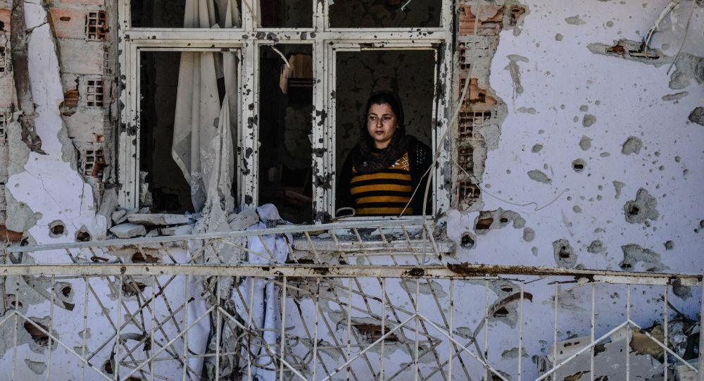 امرأة واقفة تنظر عبر نافذة بيتها المدمر في سيزر، جنوب شرق تركيا، 8 مارس/ آذار 2016.