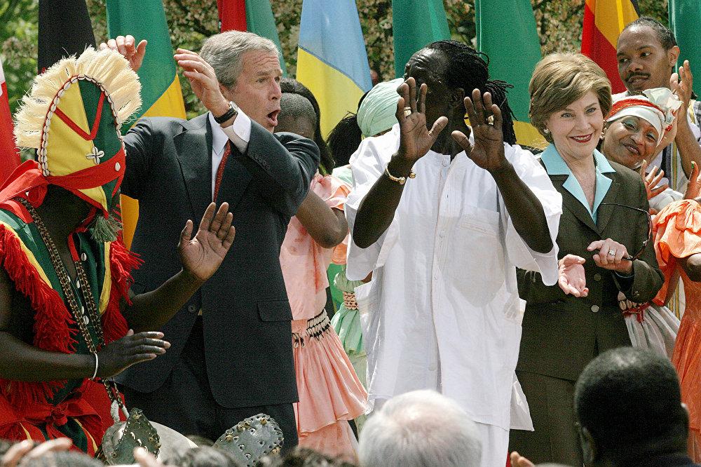 الرئيس الأمريكي جورج بوش (الابن) والسيدة الأولى لورا بوش يؤديان رقصة مع فريق موسيقي أفريقي بحديقة روز بالبيت الأبيض، واشنطن، 25 إبريل/ نيسان 2007.