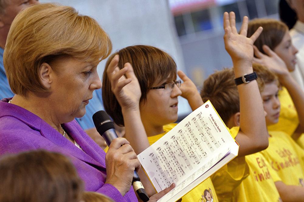 مستشارة ألمانيا أنجيلا ميركل تغني مع الأطفال خلال فعالية عامة في حديقة كانسيلري في برلين، 23 أغسطس/ آب 2009.