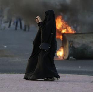 امرأة تلتقط صورة للاشتباكات والتصادمات بين الشرطة والمتظاهرين في البحرين، 5 ابريل/ نيسان 2016.