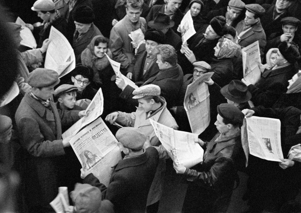 سكان موسكو يحملون الجرائد ويرأون حول أول رائد إلى فضاء في العالم يوري غاغارين