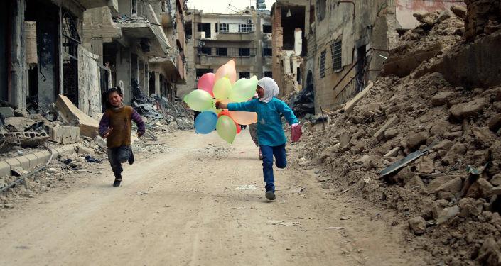 أطفال يلعبون بين دمار الحرب بالضواحي الشرقية للعاصمة السورية دمشق، 9 أبريل/ نيسان 2016