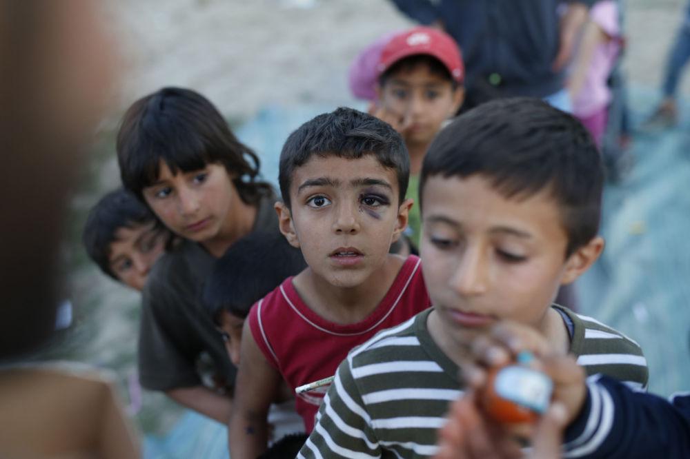 الأطفال المهاجرون يقفون في طابور للحصول على الألعاب في مخيم للاجئين باليونان، 17 أبريل/ نيسان 2016.