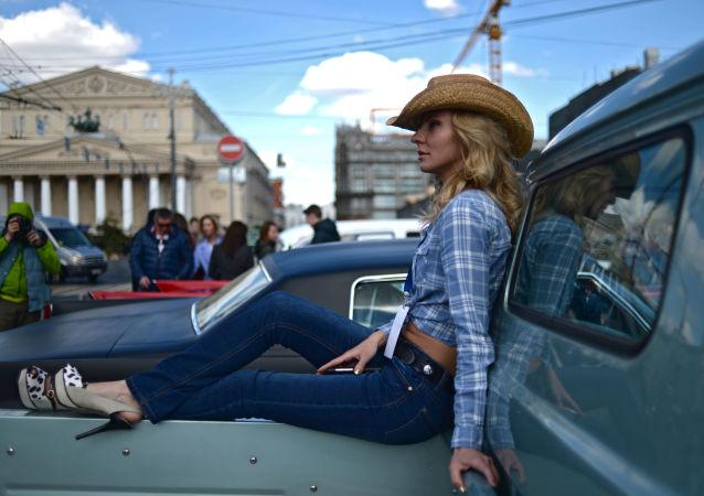 فتاة تستعرض السيارات الكلاسيكية في معرض موسكو للسيارات القديمة