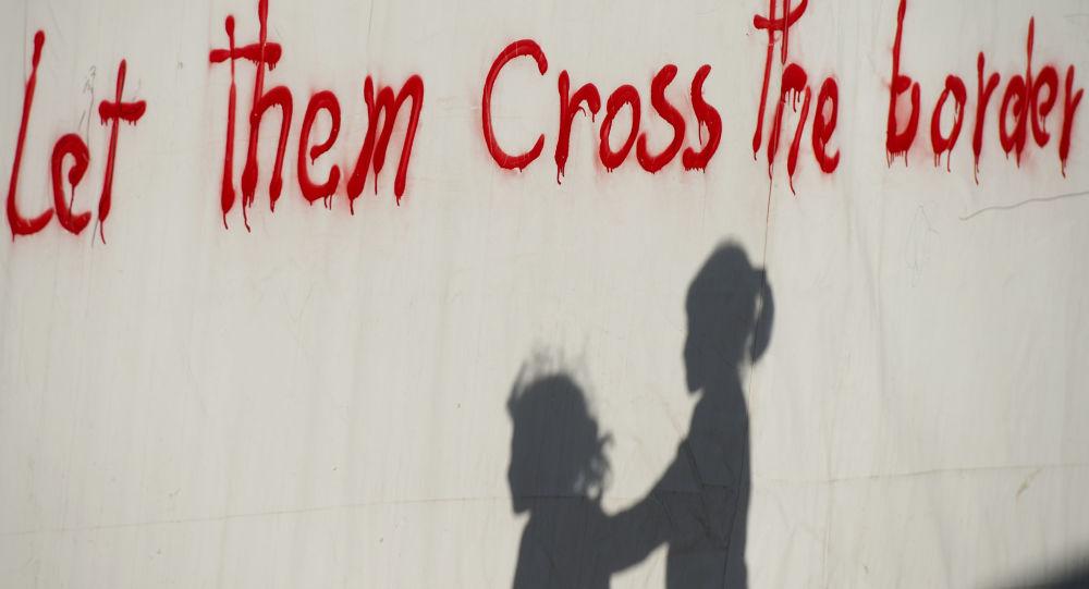 خيال أطفال لاجئين ينعكس على حائط بالقرب من قرية إيدوميني اليونانية، مكتوب عليها فلنعبر هذا الحاجز!، 4 مايو/ آيار 2016.