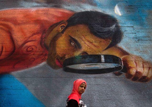 امرأة تمر بجوار جدارية كبيرة في إحدى شوارع بيروت، لبنان 4 مايو/ آيار 2016