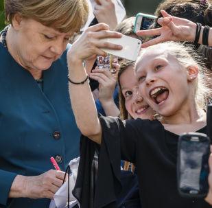 تلاميذ يأخذون صور سيلفي على خلفية أنجيلا ميركل في برلين، 3 مايو/ آيار 2016.