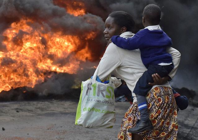 امرأة تحمل طفلها وتمر بالعجلات الحارفة في شوارع نيروبي بكينيا، 23 مايو/ آيار 2016.