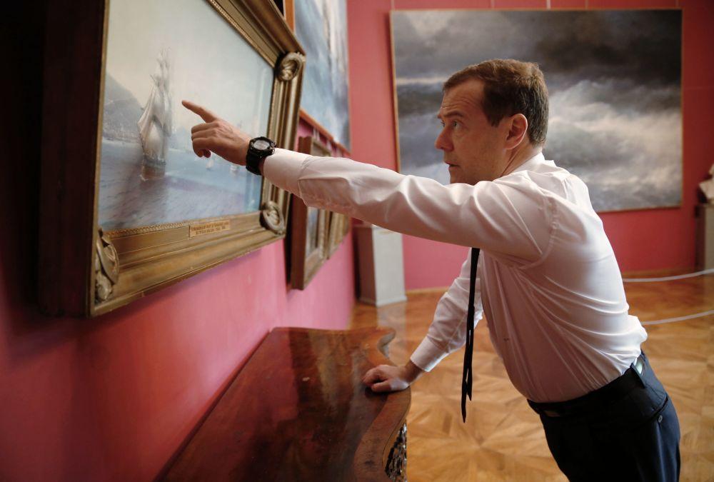 رئيس الوزراء الروسي دميتري ميدفيديف يقف إلى جوار لوحة أسطول البحر الأسود قبل حرب القرم للفنان الروسي إ. ك. آيفازوفسكي