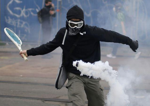 التنس - متظاهر يقوم بضربة تنس لقنبلة غازية مسيّلة للدموع في نانت، فرنسا 2 يونيو/ حزيران 2016.