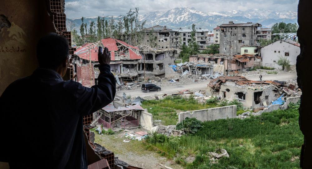 رجل يقف على خلفية ركام المباني في المنطقة التي تعرضت للاشتباكات بين القوات التركية والكردية في مدينة يوكسيكوفا بالقرب من الحدود مع العراق وإيران، 30 مايو/ آيار 2016.