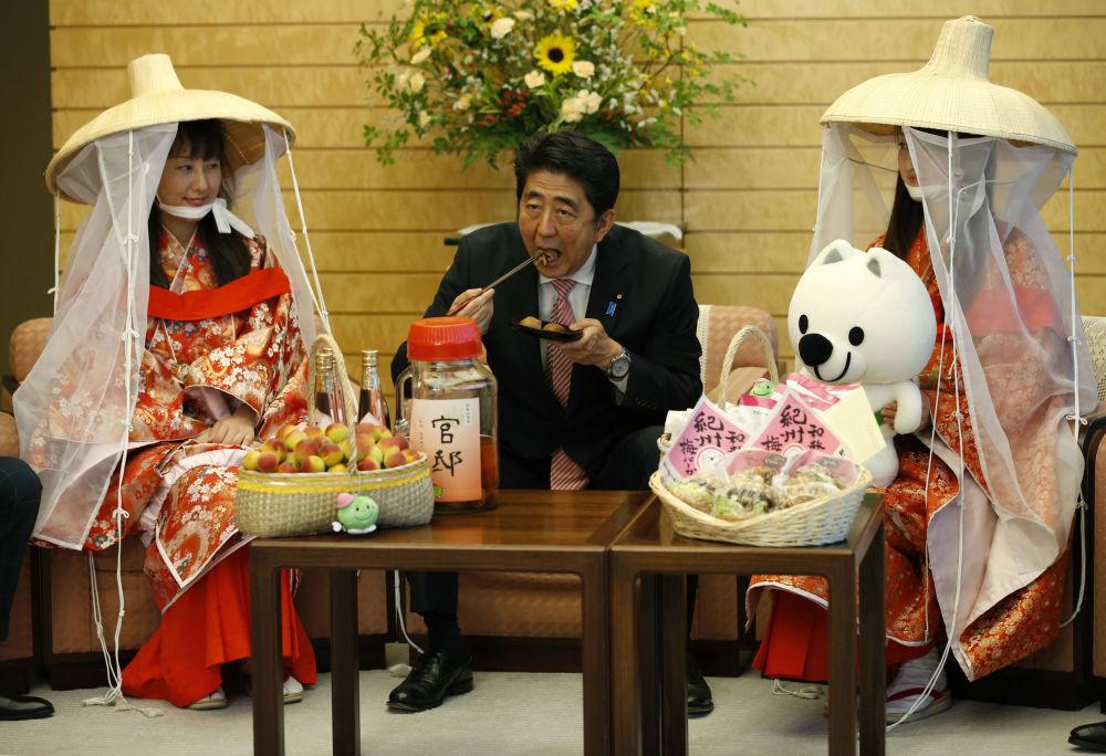 رئيس الوزراء الياباني شينزو آبي خلال تناوله فاكهة الخوخ، عام 2015