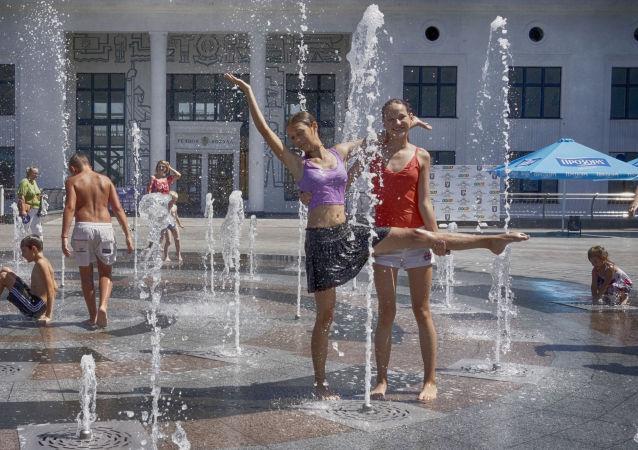 فتيات يلعبون وسط نافورة مياة لارتفاع درجات الحرارة في مدينة كييف، أوكرانيا 13 يوليو/ تموز 2016