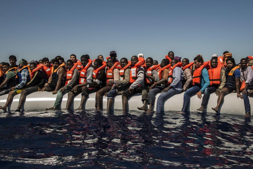 لاجئون من إرتيريا ومالي وبنغلادش (ودول أخرى) ينتظرون قارب نجاة في البحر الأبيض المتوسط على بعد 27 كم من شواطئ ليبيا، يوليو/ تموز 2016