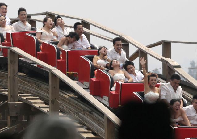 أزواج صينيون يحتفلون بزواجهم في مدينة الملاهي، الصين.