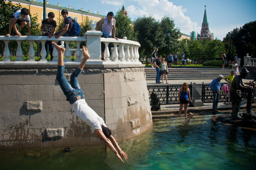 الكبار والصغار يسبحون في نافورة المياه غيروي سكازك (أبطال القصص) على ساحة مانيجنايا في موسكو