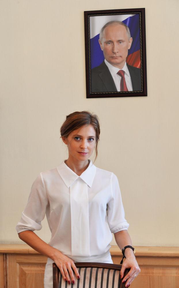 المدعي العام لجمهورية القرم نتاليا بوكلونسكايا على خلفية صورة للرئيس فلاديمير بوتين