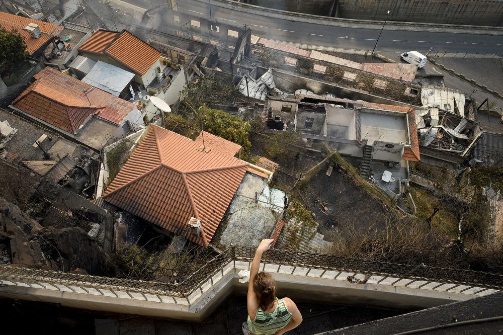 امرأة تقف على شرفة منزلها المطل على آثار حريق لمنزل مجاور في كامبو دا بارسا، جزيرة ماديرا، 10 أغسطس/ آب 2016